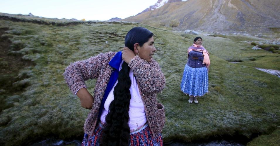 21.abr.2016 - Mulheres indígenas aimarás arrumam o cabelo antes de descer o monte Illimani, nos arredores de La Paz, na Bolívia. Há dois anos, onze delas, que trabalham como carregadoras e cozinheiras em acampamentos de montanhistas, decidiram começar seu próprio grupo de escalada