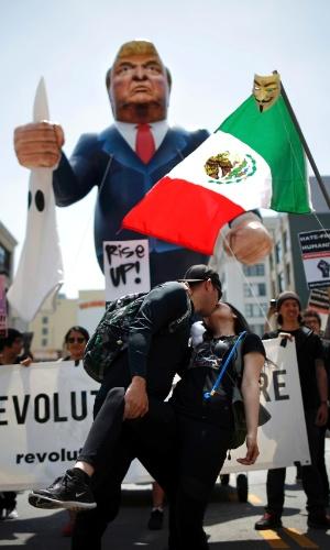 1º.mai.2016 - Casal se beija diante de boneco representando o republicano Donald Trump, possível candidato do partido à Presidência americana, em protesto por direitos de imigrantes em Los Angeles (EUA)