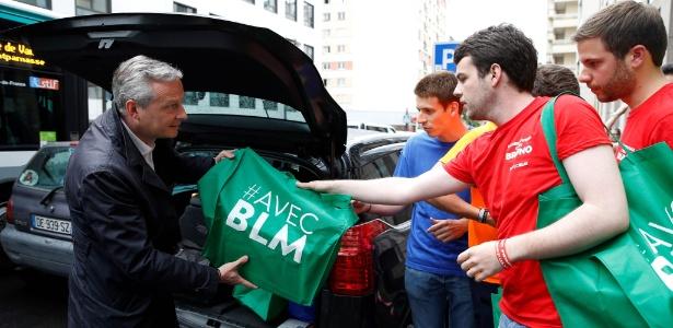 O pré-candidato à Presidência da França pelo partido Os Republicanos, Bruno Le Maire (esq), entrega material de campanha a simpatizantes, em Paris