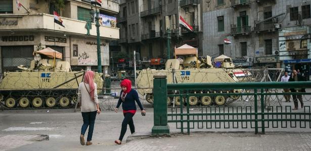Mulheres passam por veículos blindados na praça Tahrir, no Cairo (Egito)