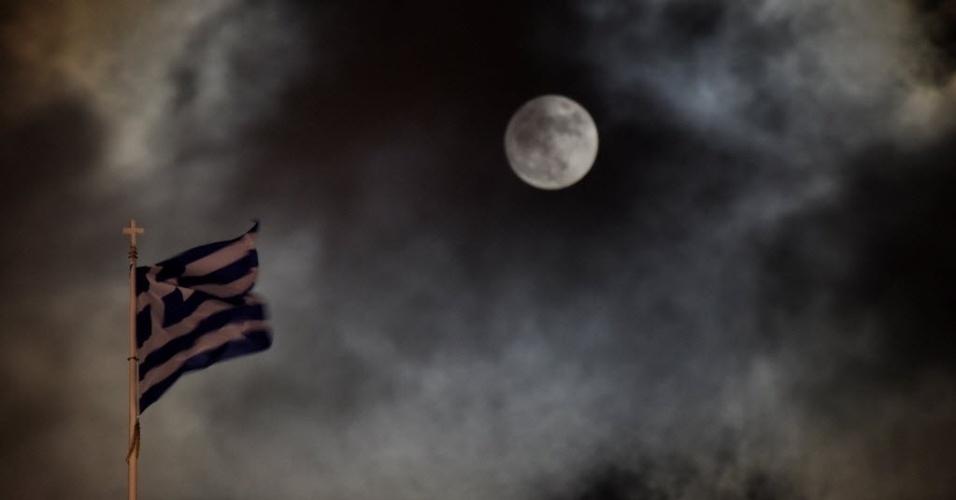 14.dez.2016 - Encoberta por nuvens, superlua aparece no céu de Atenas, na Grécia