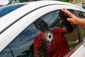 Homem observa a janela do seu carro com marca de tiro após ataque de gangues em Vitória