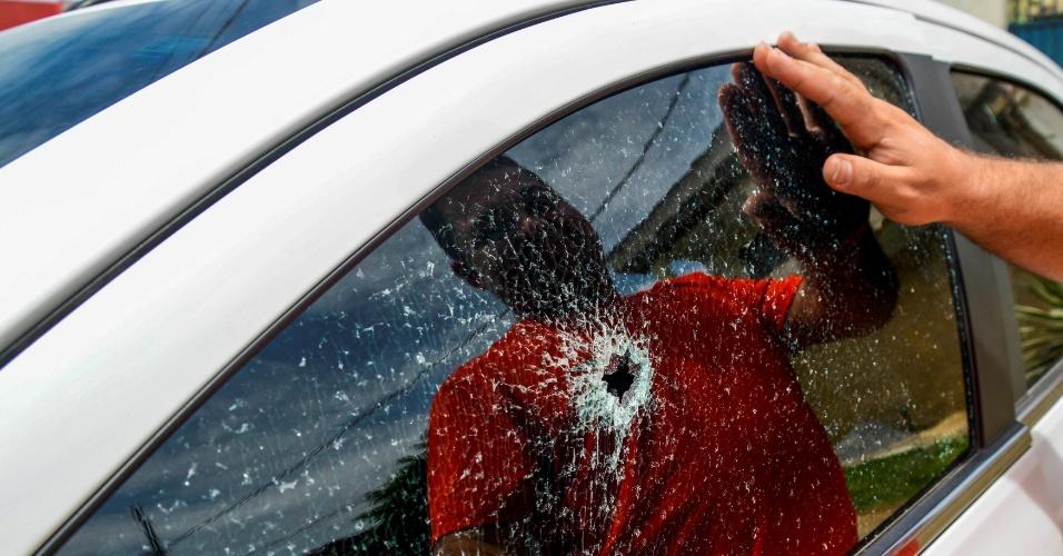 6.fev.2017 - Homem observa a janela do seu carro com marca de tiro após ataque de gangues em Vitória