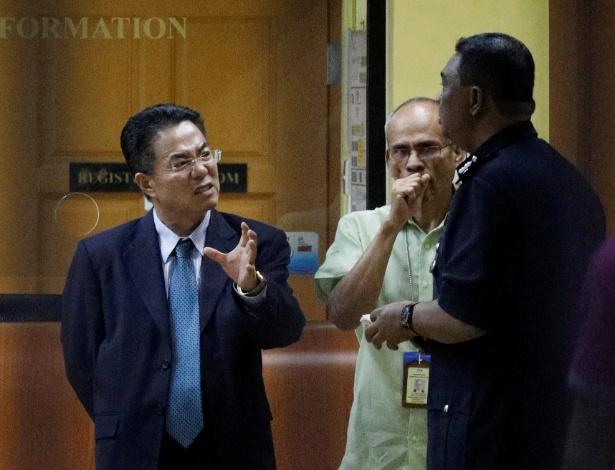 Oficial norte-coreano conversa com policiais em frente o hospital onde está o corpo do suposto Kim Jong-nam, à espera da autópsia, em Kuala Lumpur, na Malásia