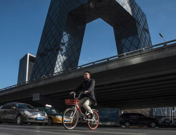 Ciclista passa com sua Mobike pelo prédio da CCTV, em Pequim (China)