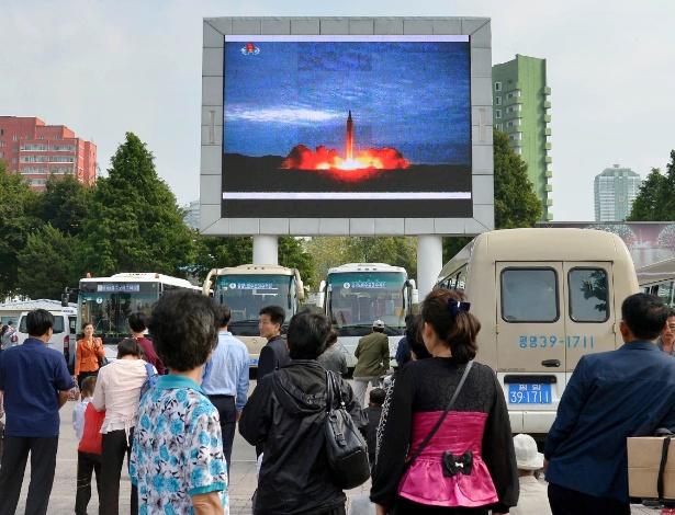Norte-coreanos observam telão com imagem de lançamento de míssil balístico, em Pyongyang - Kyodo via Reuters