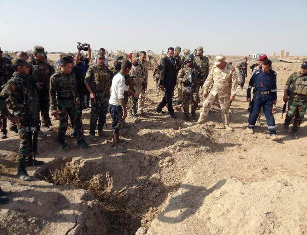 Forças iraquianas verificam uma cova suspeita de conter os restos das vítimas do grupo do Estado islâmico, perto da antiga base militar de al bakara
