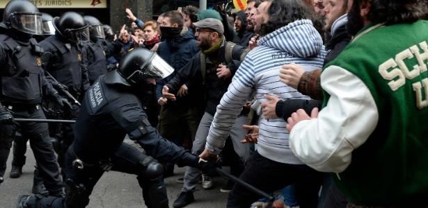 Policiais utiliza cassetete contra manifestantes que bloqueavam rua em Barcelona. Os protestos ocorrem após a prisão do líder catalão Carles Puigdemont - Josep Lago/AFP