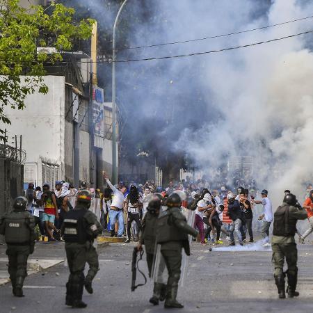 Policiais disparam em direção a manifestantes durante protesto em Caracas, na Venezuela, contra o governo de Nicolás Maduro, nesta quarta-feira (23) - Yuri Corytez/AFP