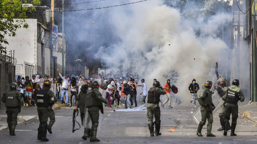 24.jan.2019 - Policiais disparam em direção a manifestantes durante protesto em Caracas, na Venezuela, contra o governo de Nicolás Maduro, nesta quarta-feira (23) - Yuri Corytez/AFP