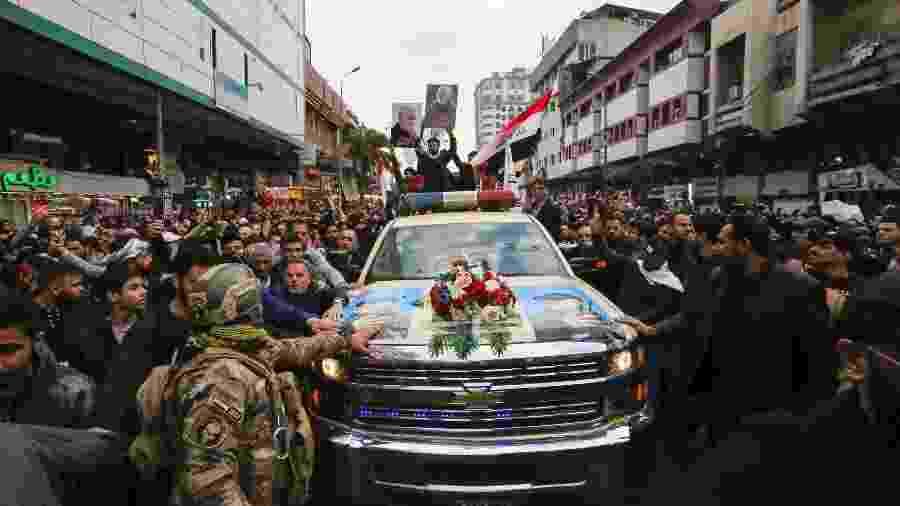 Iraquianos acompanham procissão com o caixão do comandante militar  iraquiano, Abu Mahdi al-Muhandis, em Bagdá. Ele foi morto em um ataque aéreo dos EUA na quinta-feira, na capital do Iraque - SABAH ARAR/AFP