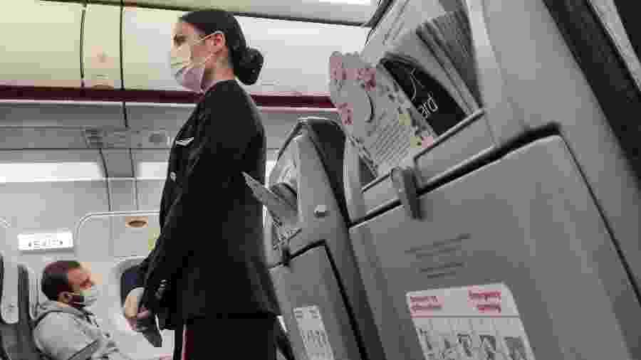 De máscara, comissária de bordo instrui passageiros dentro de avião em meio à pandemia do coronavírus - Nicolas Economou/NurPhoto via Getty Images