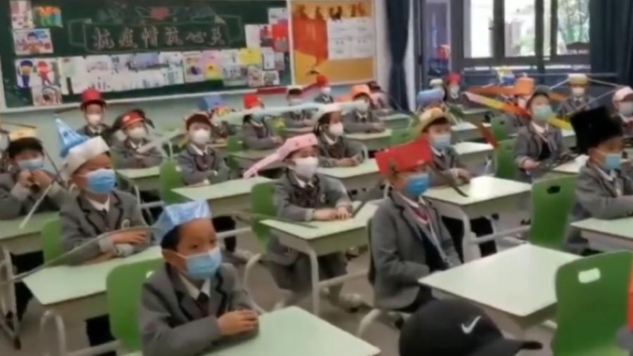 """Crianças em escola chinesa usam """"chapéu de um metro"""" - Reprodução / The Sun / Asia Wire"""