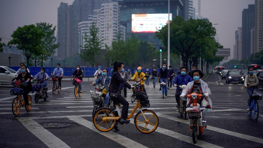 Pessoas que usam máscaras protetoras andam de bicicleta em Wuhan, a cidade chinesa mais afetada pelo surto de doença por coronavírus, na província de Hubei, na China - ALY SONG/REUTERS
