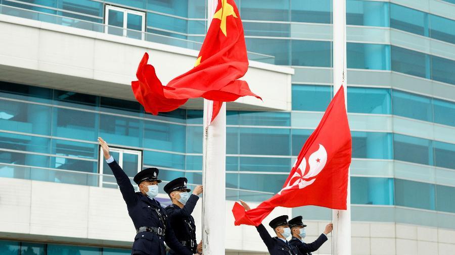 Policiais ao lado das bandeiras da China e de Hong Kong, em cerimônia oficial em Hong Kong - Tyrone Siu/Reuters