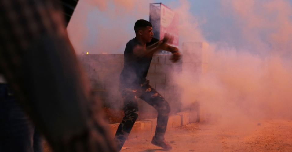 24.jul.2015 - Manifestante palestino joga bomba de gás de volta para policiais durante confronto com forças de segurança israelenses no vilarejo de Silwad, no norte de Ramallah, após uma marcha contra a construção de assentamentos na Cisjordânia