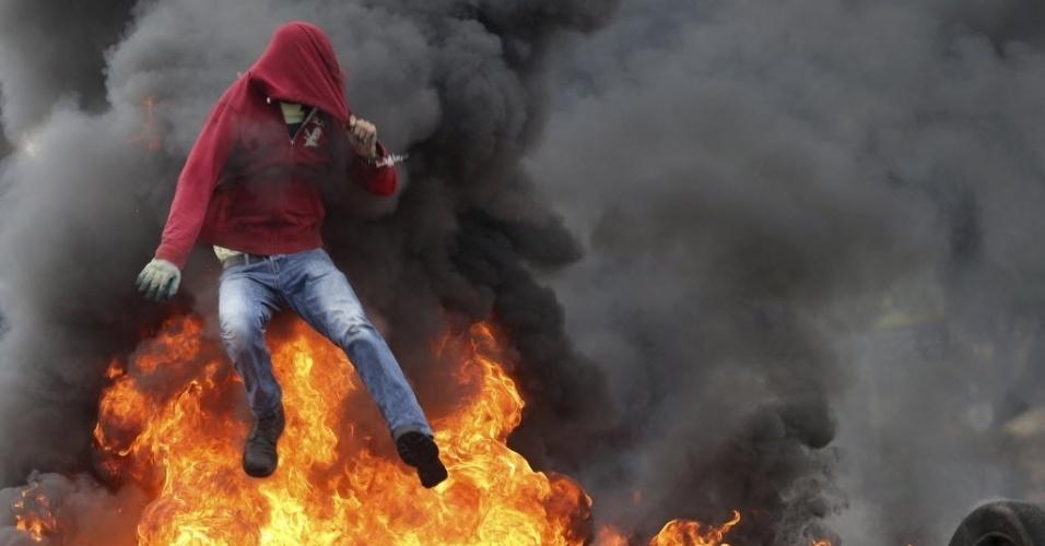 26.out.2015 - Um manifestante palestino pula uma barreira de pneus pegando fogo durante confrontos com tropas israelenses perto de assentamentos judeus de Bet El, nas proximidades de Ramallah, na Cisjordânia
