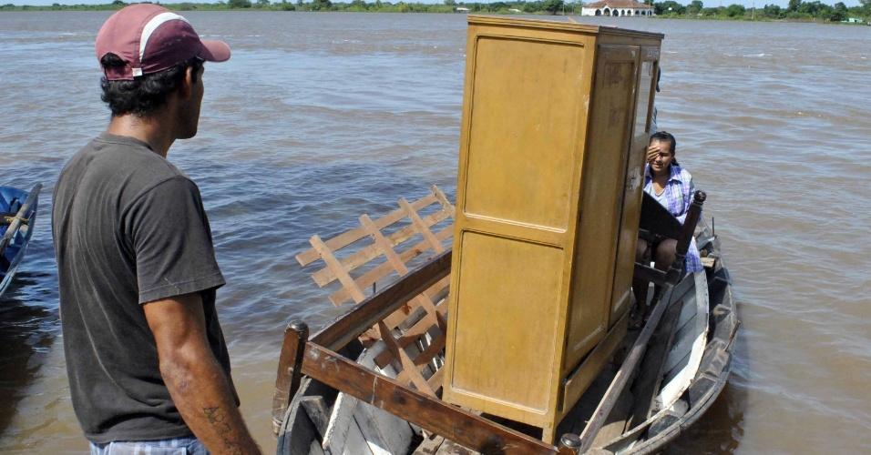 24.dez.2015 - Moradores transportam de barco seus pertences, para fugir da inundação provocada pela cheia do rio Paraguai, em Assunção. Segundo autoridades paraguaias, a cheia do rio já exigiu a remoção de 13.500 famílias em Assunção e de outras 13.000 no restante do país. Em virtude de tempestades, são 130.000 desabrigados em todo o Paraguai. O governo local qualificou a situação de