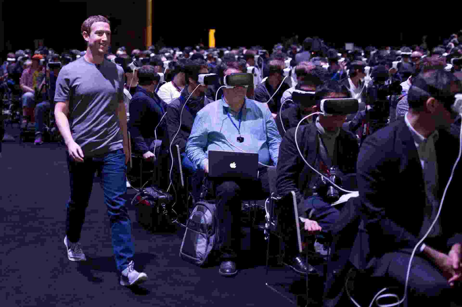 """21.fev.2016 - O criador do Facebook, Mark Zuckerberg, caminha diante de pessoas utilizando o óculos de realidade virtual Gear VR , da Samsung, no Mobile World Congress, em Barcelona, neste domingo. O norte-americano apareceu de surpresa para falar do futuro da realidade virtual, dizendo que essa será a plataforma """"mais social de todas"""". O Gear VR foi construído sobre a plataforma Oculus, adquirida pelo Facebook em 2014 - Divulgação/Facebook"""