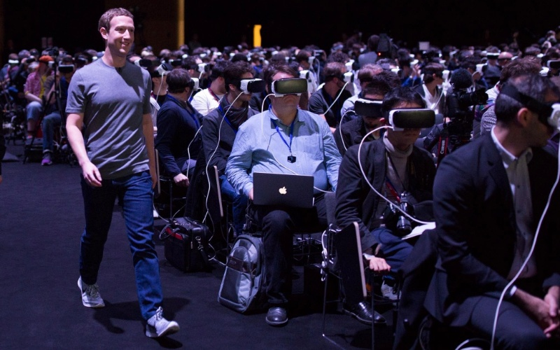 """21.fev.2016 - O criador do Facebook, Mark Zuckerberg, caminha diante de pessoas utilizando o óculos de realidade virtual Gear VR , da Samsung, no Mobile World Congress, em Barcelona, neste domingo. O norte-americano apareceu de surpresa para falar do futuro da realidade virtual, dizendo que essa será a plataforma """"mais social de todas"""". O Gear VR foi construído sobre a plataforma Oculus, adquirida pelo Facebook em 2014"""