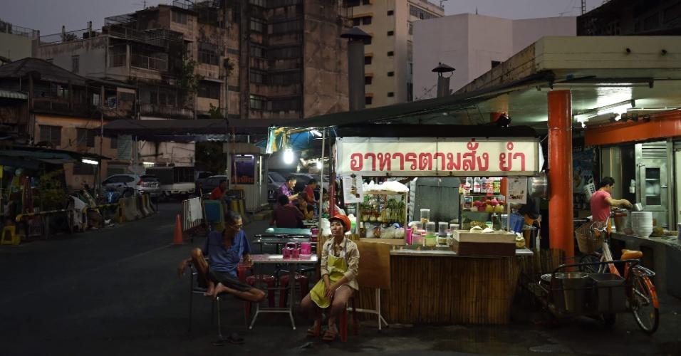 17.mar.2016 - Tailandesa espera clientes diante de seu restaurante de rua em Bancoc