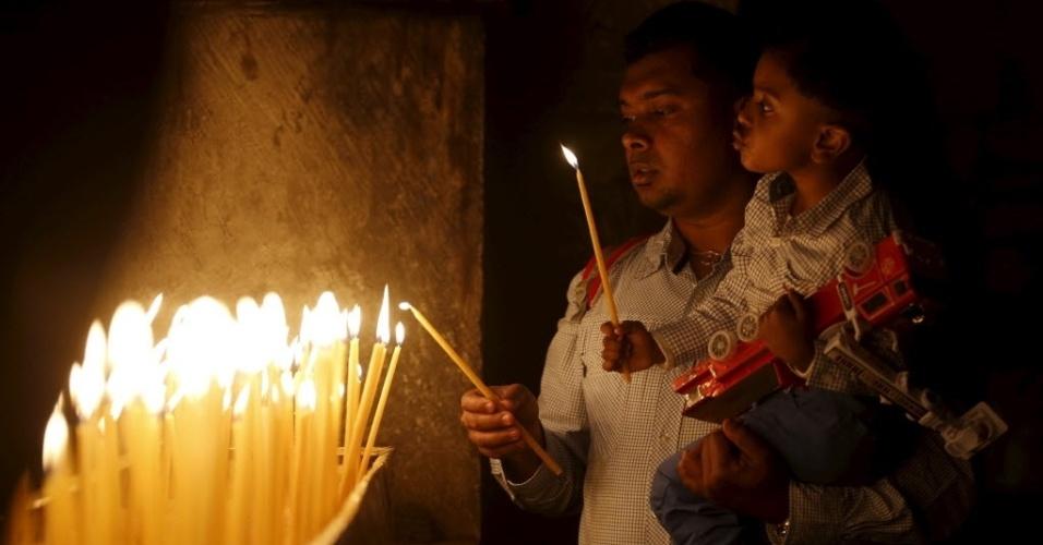 27.mar.2016 ? Um menino acende uma vela com seu pai durante missa de Domingo de Páscoa na Igreja do Santo Sepulcro em Jerusalém