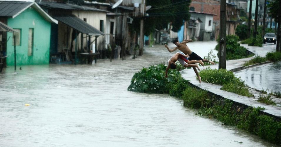 10.abr.2016 - Dupla de meninos ignora risco de prejuízo a saúde e se diverte em rua alagada na cidade de Manaus. Uma forte chuva castiga vários bairros da capital amazonense