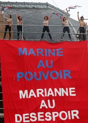 Ativistas abrem cartaz contra Le Pen