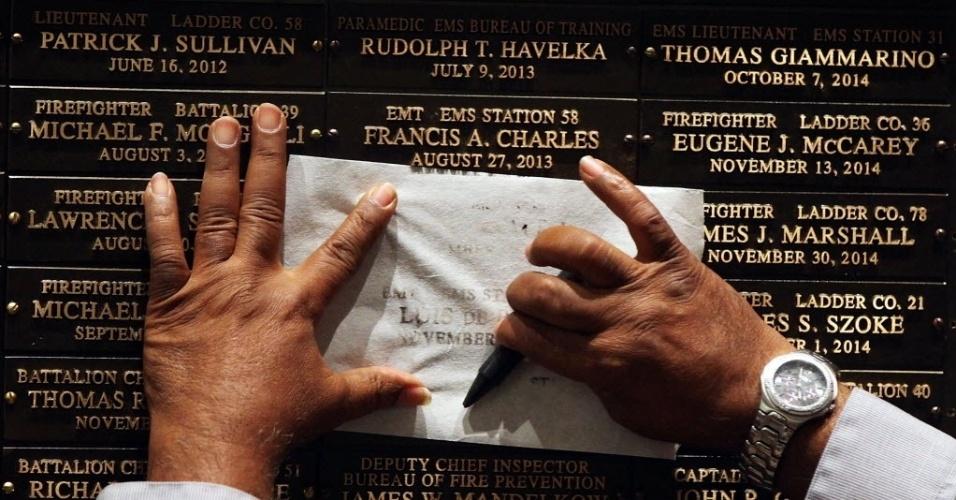 8.set.2015 - Famílias copiam os nomes de seus entes queridos em uma cerimônia dos Corpos de Bombeiros de Nova York, nos Estados Unidos, onde 21 vítimas de mortes relacionadas a queda do World Trade Center tiveram seus dados adicionados a um memorial. No total, a parede conta 89 nomes de pessoas que morreram de doenças relacionadas ao trabalho durante ou após o ataque do 11 de setembro