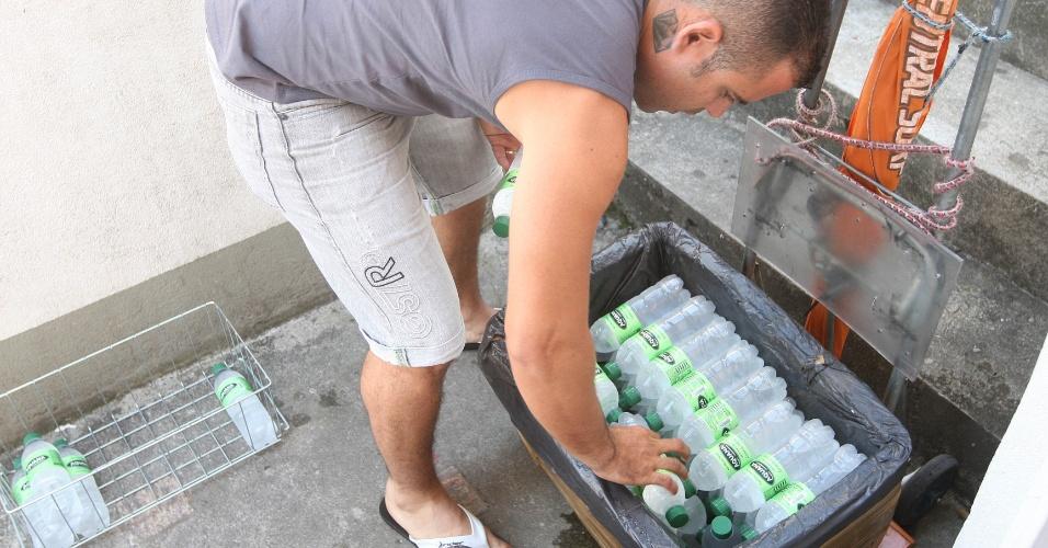 15.out.2015 - Depois do café, Jairo de Freitas arruma as garrafas que venderá no dia. São cerca de 120 arrumadas em dois isopores