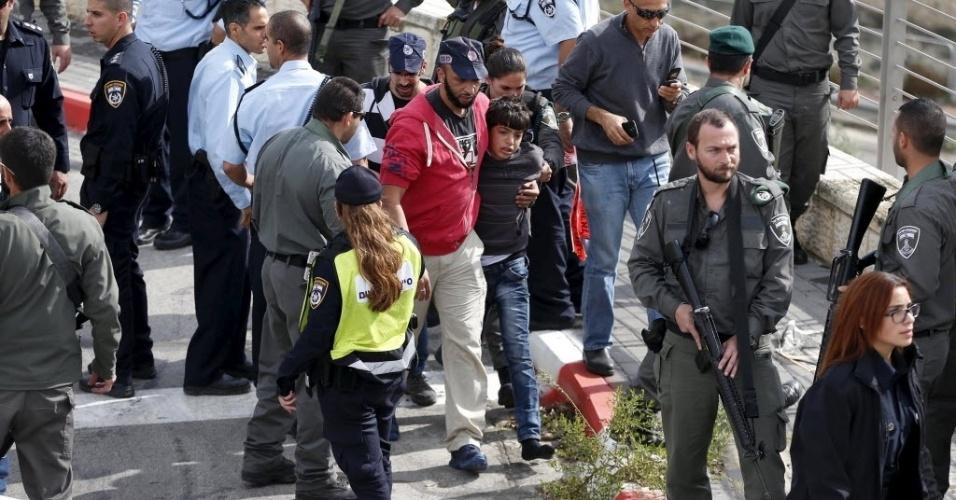 10.nov.2015 - Menino palestino que teria esfaqueado um segurança israelense é levado por guardas de Israel em Pisgat Zeev, região palestina vizinha à Jerusalém ocupada por Israel. Segundo a polícia israelense, dois palestinos, de 12 e 13 anos, atacaram um segurança a facadas, que teria reagido e baleado um deles
