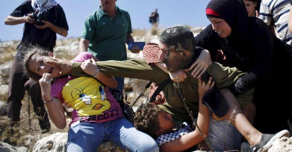 28.ago.2015 - Palestinos tentam impedir um soldado israelense de deter um menino durante protesto contra os assentamentos judaicos na aldeia de Nabi Saleh, na Cisjordânia