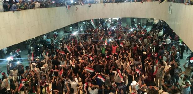 Seguidores do clérigo xiita do Iraque Moqtada al-Sadr lotam dependências do edifício do parlamento após milhares deles invadirem a Zona Verde da capital, Bagdá. O protesto ocorreu depois que legisladores não conseguiram convocar uma votação sobre a reforma do governo
