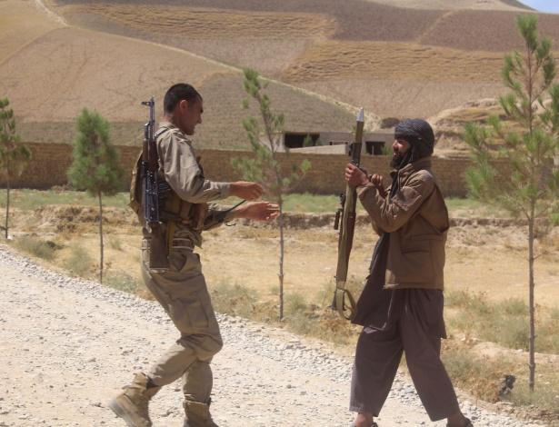 O combatente do Taleban Said Muhammad (dir) se rende e entrega as armas ao pai Abdul Basir, comandante da milícia do governo afegão, após anos de combates entre os dois