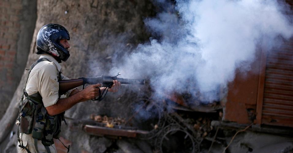 23.set.2016 - Policial indiano, usando capacete improvisado, atira bomba de gás lacrimogênio na direção de manifestantes em Srinagar, na região da Caxemira