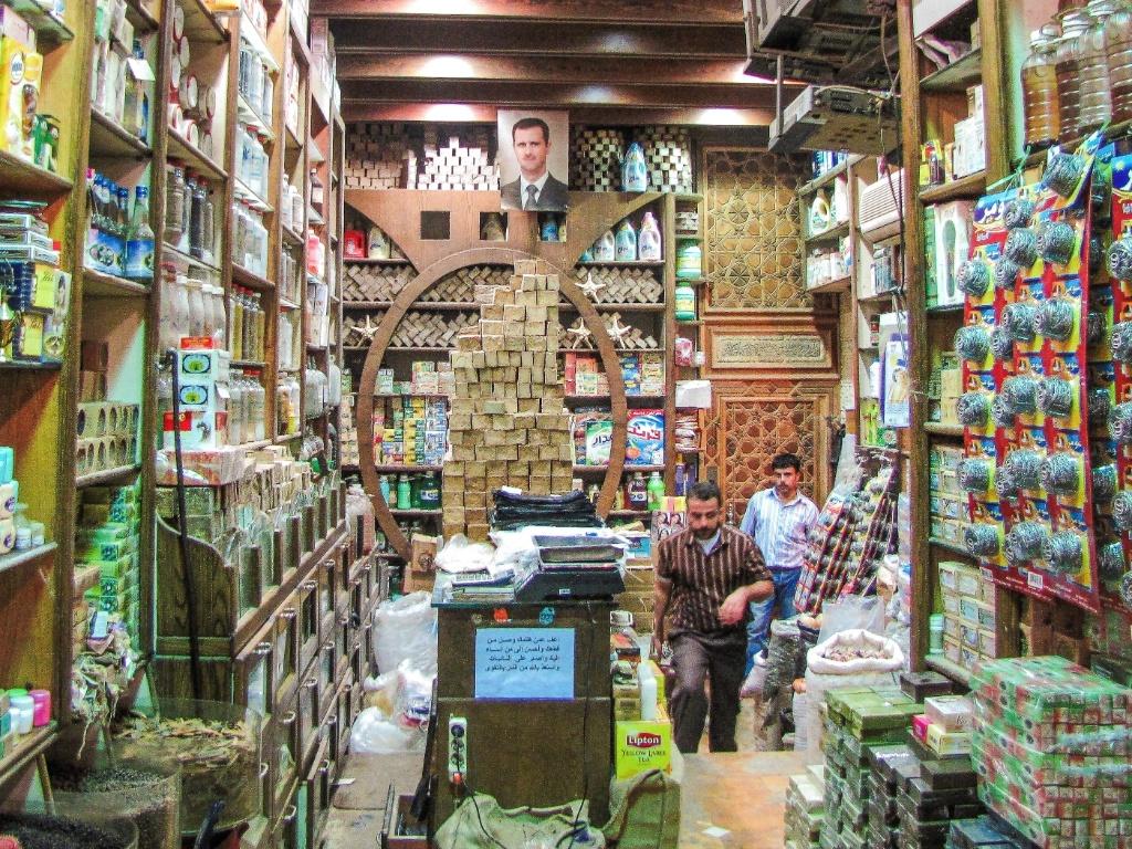 Loja no souq de Aleppo, com os tradicionais sabões locais e foto do Bashar al-Assad na parede. Antes da guerra, era politicamente adequado exibir fotos do presidente-ditador em negócios e locais públicos