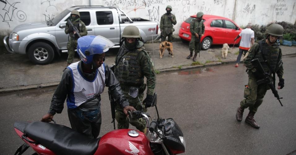 23.fev.2018 - Militares revistam motoqueiro durante operação na favela Vila Kennedy, na zona oeste do Rio de Janeiro. Cerca de 3.200 militares estão executando ações de cerco, desobstrução de vias e ações de estabilização na Vila Kennedy e em mais duas favelas da região
