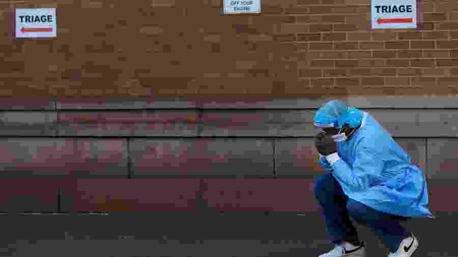 Um profissional de saúde faz uma pausa fora do centro de emergência do Maimonides Medical Center durante o surto da doença por coronavírus no bairro do Brooklyn em Nova York, EUA - ANDREW KELLY/REUTERS