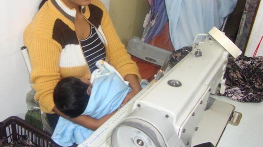 Jovem resgatada cuida do filho recém-nascido enquanto trabalha em máquina de costura - Bianca Pyl/Repórter Brasil