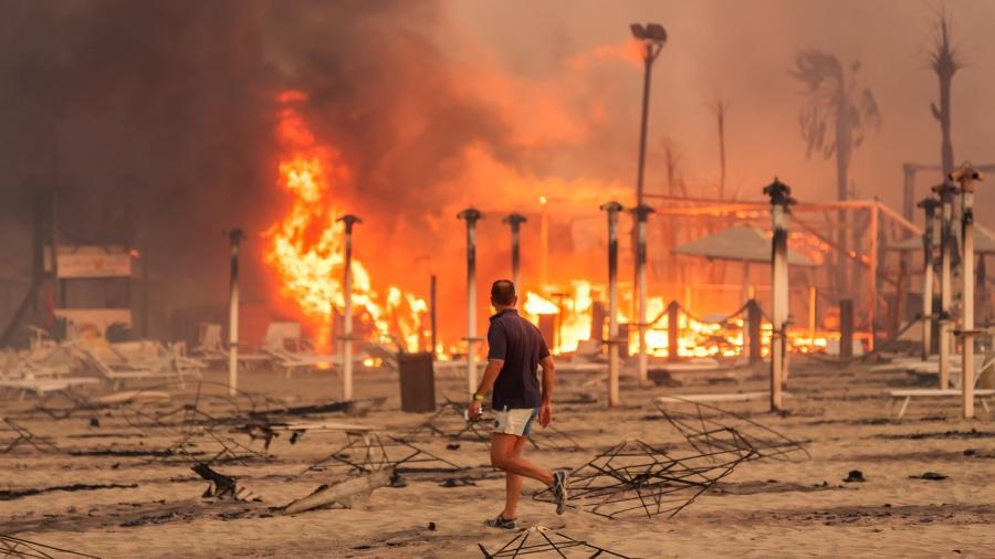 Homem observa fogo na praia de Le Capannie, em Catania, na Sicília, na tarde de sábado (31). A Itália registrou mais de 800 focos de incêndio no fim de semana - Roberto Viglianisi/via REUTERS