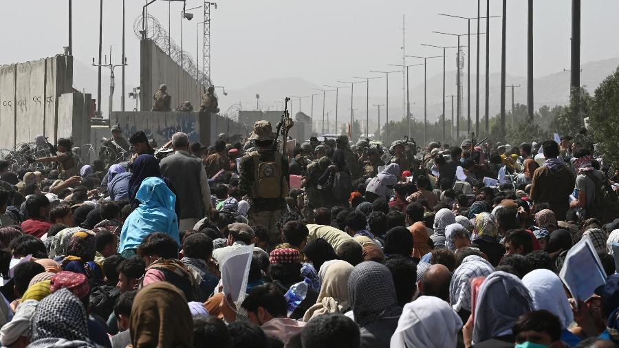 20.ago.2021 - Afegãos se reúnem em uma estrada perto da parte militar do aeroporto de Cabul, na esperança de fugir do país após a tomada militar do Taleban no Afeganistão - Wakil Kohsar/AFP