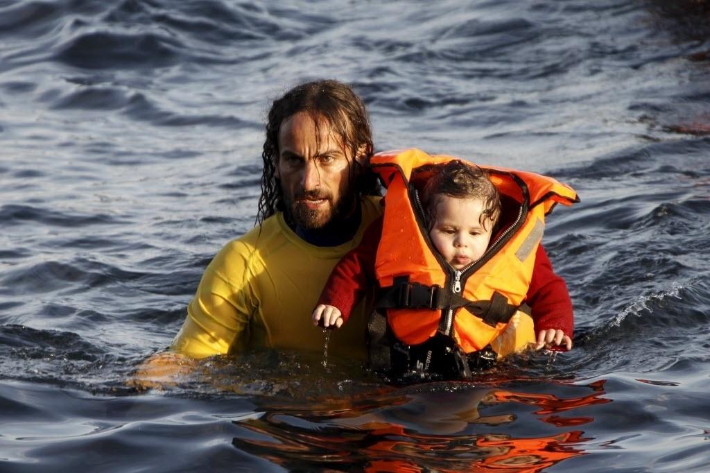 30.out.2015 - Voluntário leva bebê para terra firme após naufrágio de embarcação próximo à ilha grega de Lesbos. Dois novos naufrágios de embarcações procedentes da Turquia deixaram mortos pelo menos 22 refugiados, incluindo 13 crianças