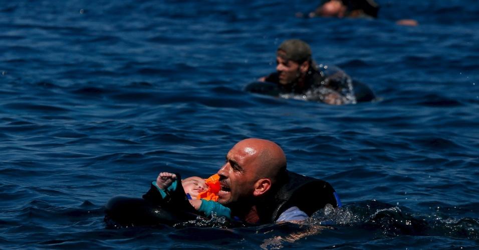 12.set.2015 - Refugiado sírio segura um bebê enquanto nada em direção à ilha de Lesbos, na Grécia