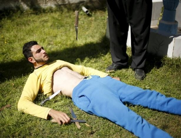 7.mar.2016 - Para demonstrar que é o homem mais forte e resistente da faixa de Gaza, Mohammad Baraka deita no chão e deixa que derrubem facas com as pontas apontadas para sua barriga. É fácil ver porque o jovem é comparado com o personagem bíblico Sansão, que tinha força descomunal