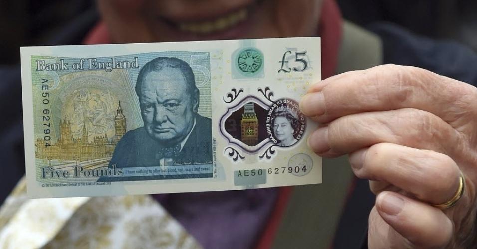 """2.jun.2016 - Nova nota de plástico de cinco libras com homenagem ao estadista britânico Winston Churchill é apresentada no Blenheim Palace, antiga casa do líder britânico, em Oxfordshire, na Inglaterra. A nota traz a efígie do político e uma famosa frase proferida por ele: """"não tenho nada a lhes oferecer senão sangue, trabalho, lágrimas e suor"""". A rainha Elizabeth 2ª estampa o outro lado da cédula, que é a primeira de plástico lançada no Reino Unido. O Banco da Inglaterra pretende substituir as notas de papel por notas de plástico, consideradas mais duráveis e seguras. A nota entrará em circulação em Setembro. Uma cédula de plástico homenageando a escritora Jane Austen deve ser lançada em 2017"""