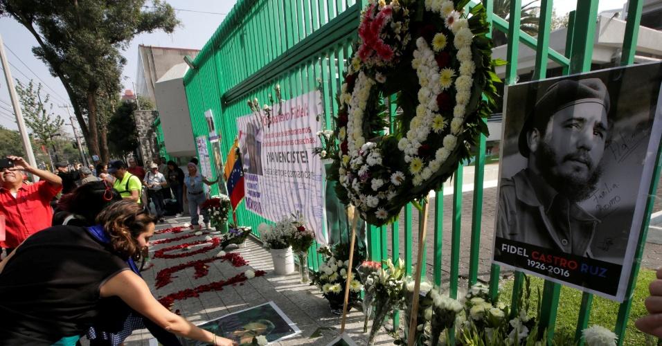 27.nov.2016 - Fotos de Fidel Castro e flores vão sendo colocadas em frente à embaixada de Cuba na Cidade do México