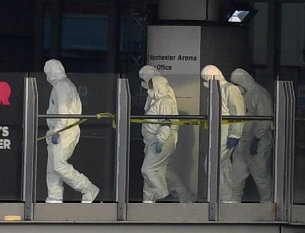 Agentes forenses passam por passarela que liga a estação Victoria e a Manchester Arena