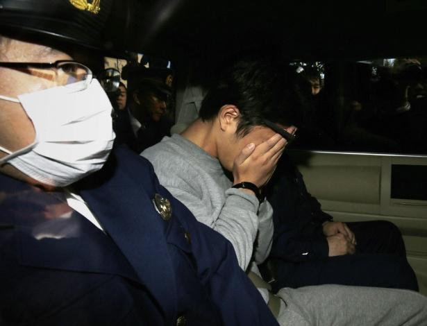 Shiraishi esconde o rosto ao ser transportado pela polícia em 1º de novembro, em Tóquio