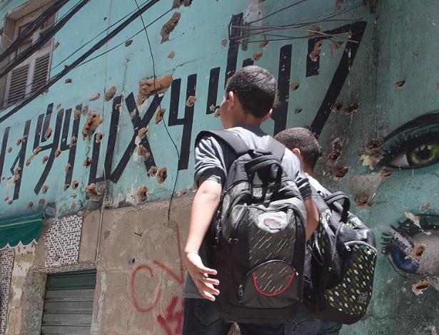 17.nov.2017 - Estudantes passam diante de casa crivada de balas na rua 2 na Rocinha