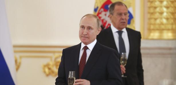 Vladimir Putin e, ao fundo, o ministro do Exterior russo Sergei Lavrov